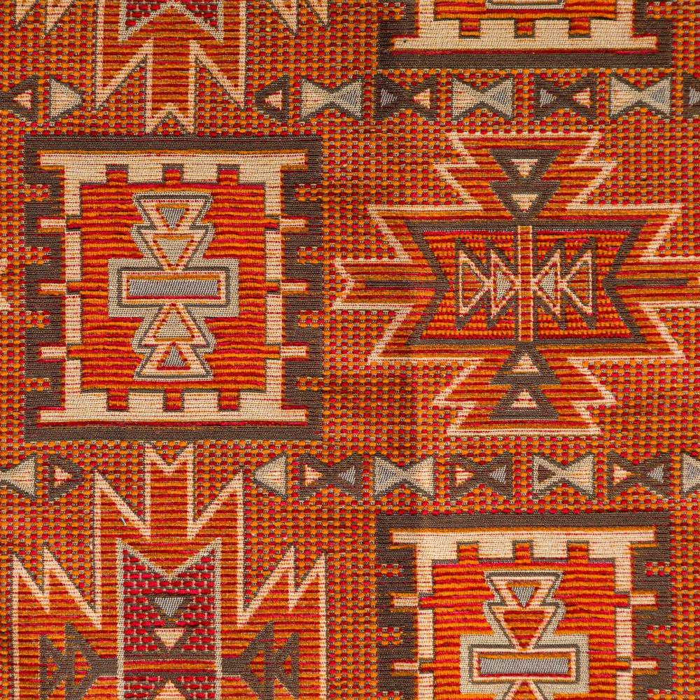 een kelim achtige meubelstof met oranje en licht bruine kleuren