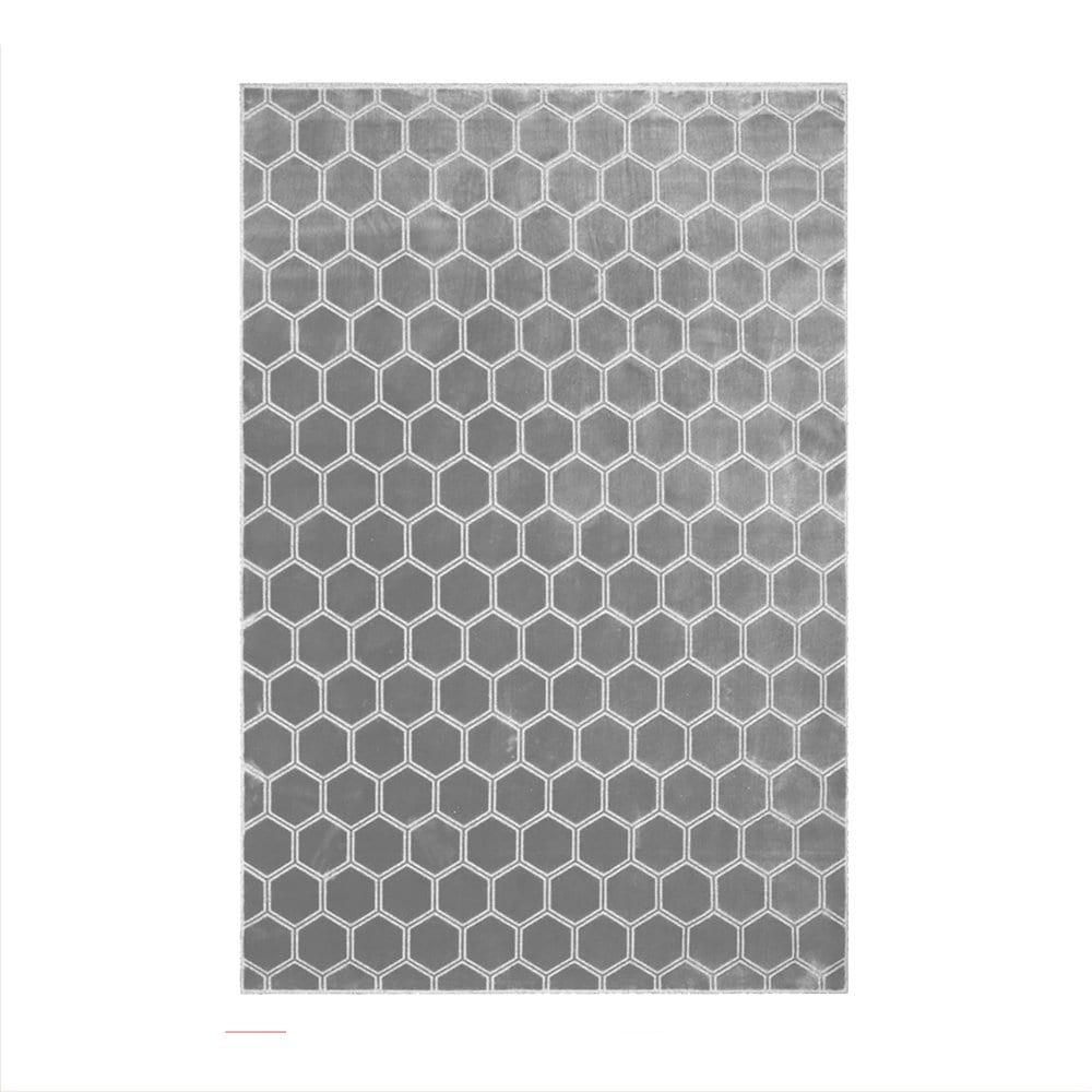 een zilver vloerkleed met een honingraat dessin